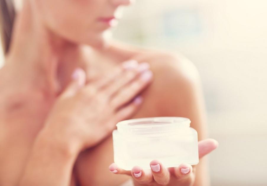une femme enduit ses seins de crème