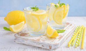 Verres d'eau avec du citron et des pailles