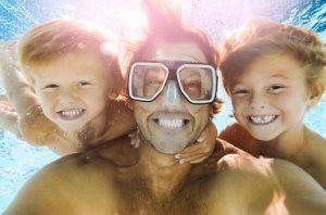 un homme avec deux enfants plonge sous l'eau