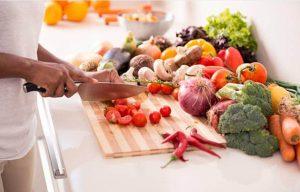 femme coupant des tomates et des légumes