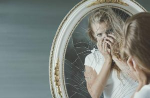 Femme déçue et miroir fissuré