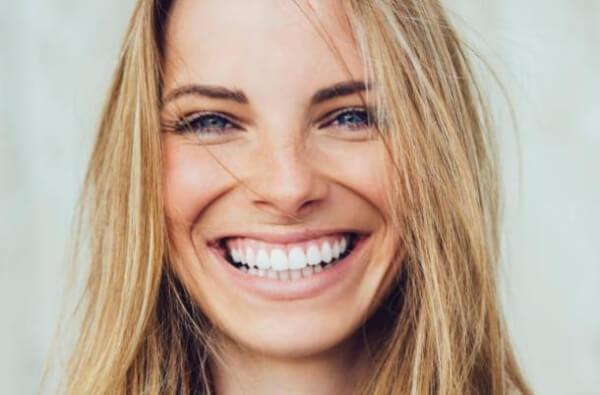 La femme souriante aux dents blanches