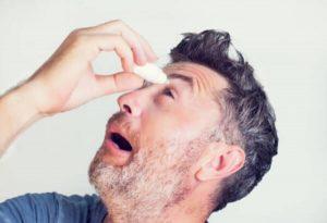 un homme met des gouttes pour les yeux