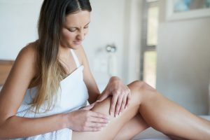 une femme avec de la cellulite appuie sa peau sur ses jambes
