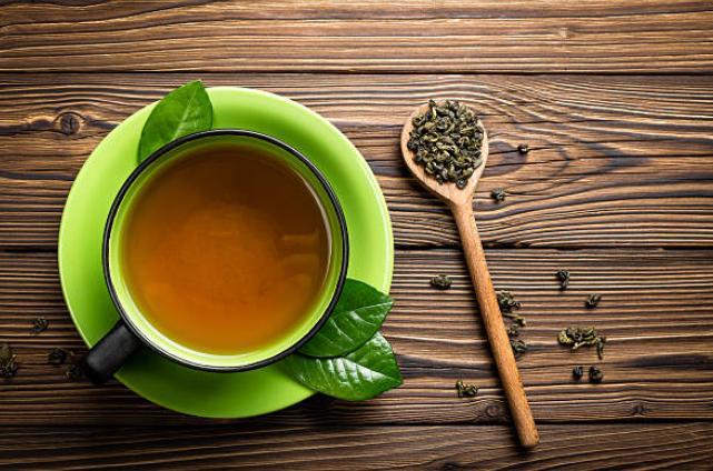Une tasse de thé, une cuillère et des feuilles de thé vert